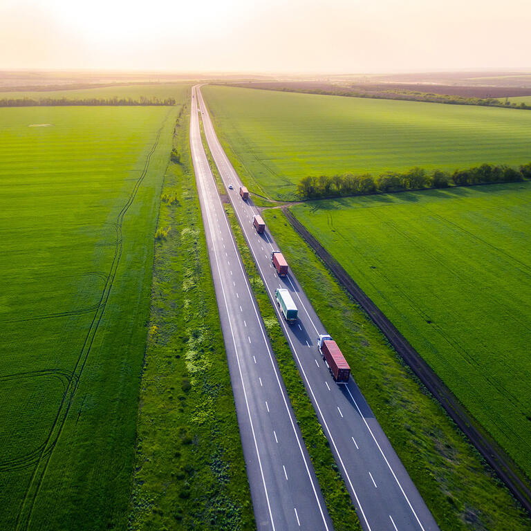 trucks on the higthway sunset. cargo delivery driving on asphalt road along the green fields. seen from the air. Aerial view landscape.