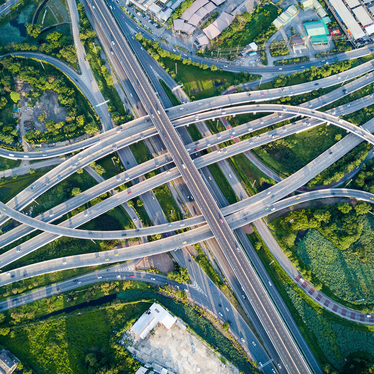 Aerial view of road interchange or highway intersection with busy urban traffic speeding on the road.