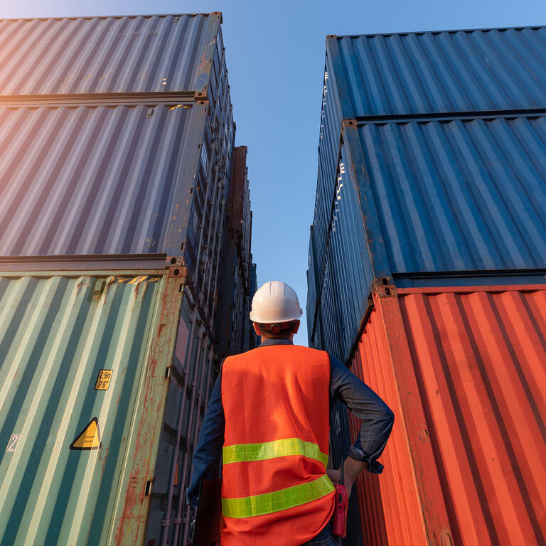 The abstract image of the engineer standing in shipping container yard and copy space. the concept of engineering, shipping, shipyard, business and transportations