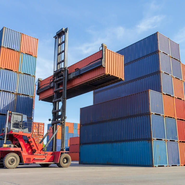 Forklift handling container box loading to truck in shipping yard with cargo container background.