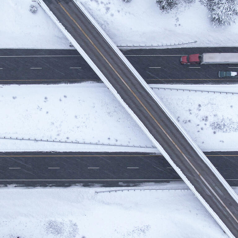 Flying above a highway overpass in USA during an intense blizzard.