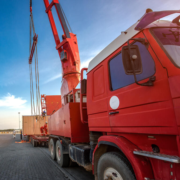 transportation of the logistics services on the heavy lift cargo transfer loading from the ship carry onto the lowbase trailer by professional working teams in port terminal