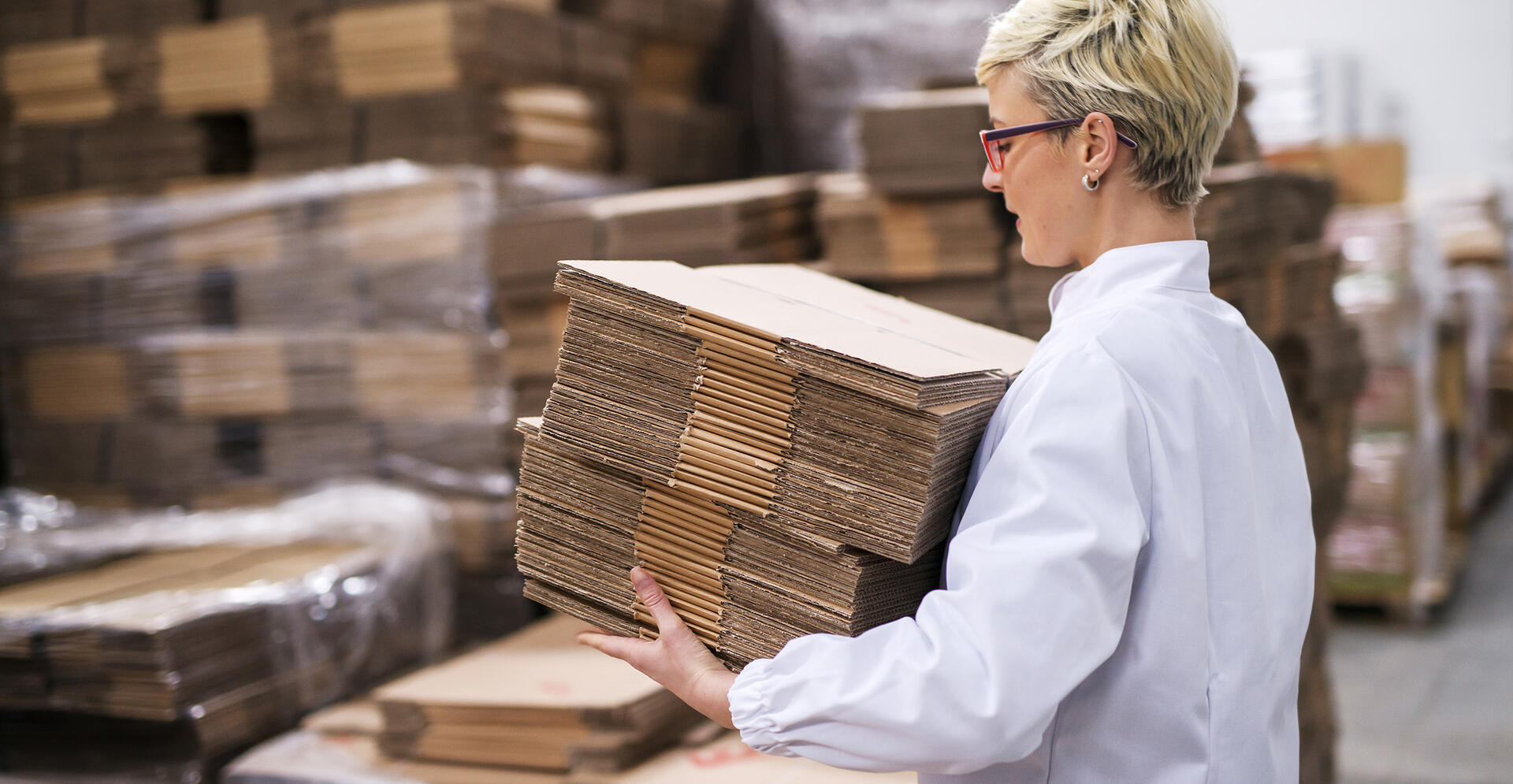 Woman carrying unmade cardboard boxes. Side view, warehouse interior.